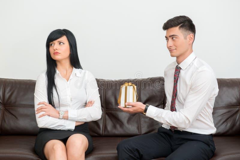 企业夫妇坐沙发在办公室 免版税库存照片