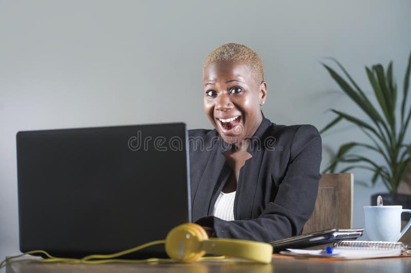 企业夹克工作的年轻可爱和愉快的成功的黑人美国黑人的妇女快乐在办公室便携式计算机书桌 免版税库存图片
