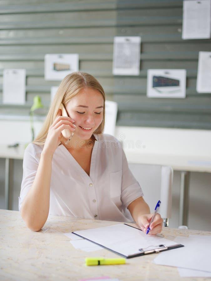 企业女孩在电话里说,当坐在她的笔记后时 图库摄影