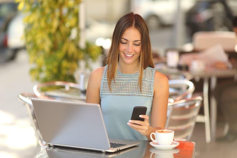 企业家与一台电话和膝上型计算机一起使用在咖啡店 库存照片