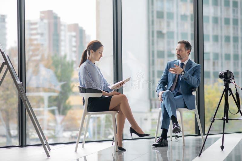 企业家和记者在拍摄成功时谈论成功 免版税库存照片