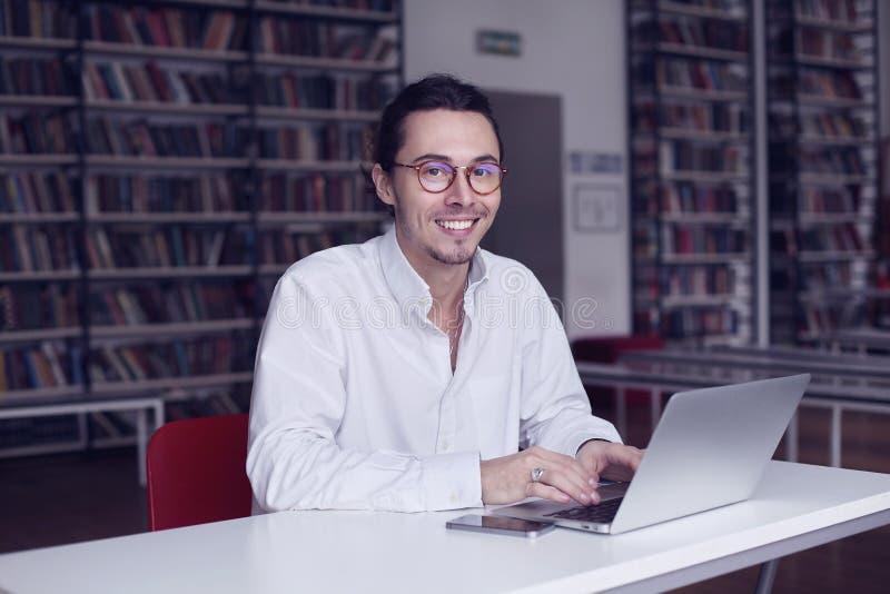 年轻企业家,微笑和研究有书的膝上型计算机的大学生在科学论文在图书馆里 免版税库存图片