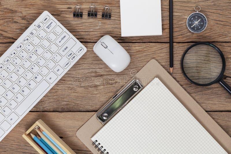 企业工作场所办公桌桌和键盘,老鼠,白皮书,笔记本,铅笔,在木桌上的指南针企业对象  库存图片