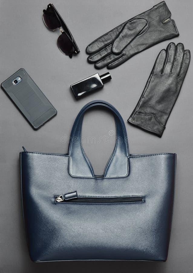 企业布局,顶视图夫人的,在灰色背景的小配件辅助部件 皮包,智能手机,太阳镜,手套 库存图片