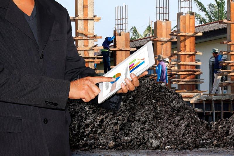 企业建造场所、商人使用片剂和被弄脏的背景建筑工人 免版税库存照片