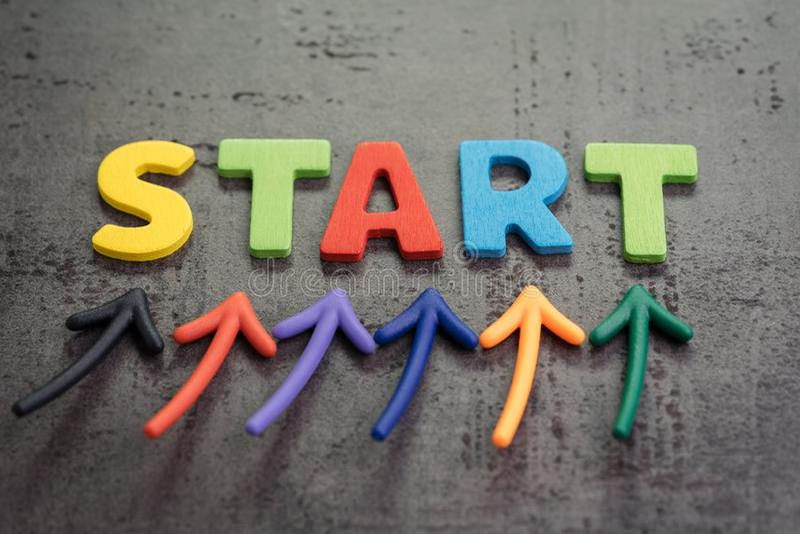 企业开始或开始新的生活旅途概念,五颜六色的箭头指向由在黑板水泥墙壁上的词开始决定 库存照片