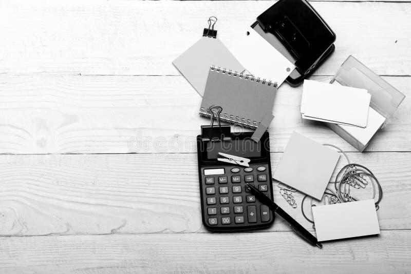企业想法概念 笔记本和穿孔机在笔附近在白色木背景 免版税库存照片