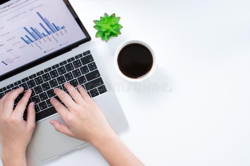 企业手的顶视图分析在一个手提电脑屏幕上的图表在一张现代白色书桌上 一个平的拷贝区域 库存图片