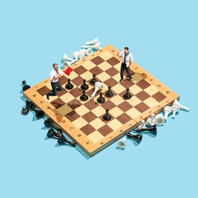 企业政策制定概念 微型人民:走小商人的形象站立和在棋枰与 库存图片