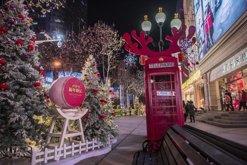 企业新年装饰,有鹿角鹿角和圣诞树的,夜视图紫色红色电话亭 免版税图库摄影