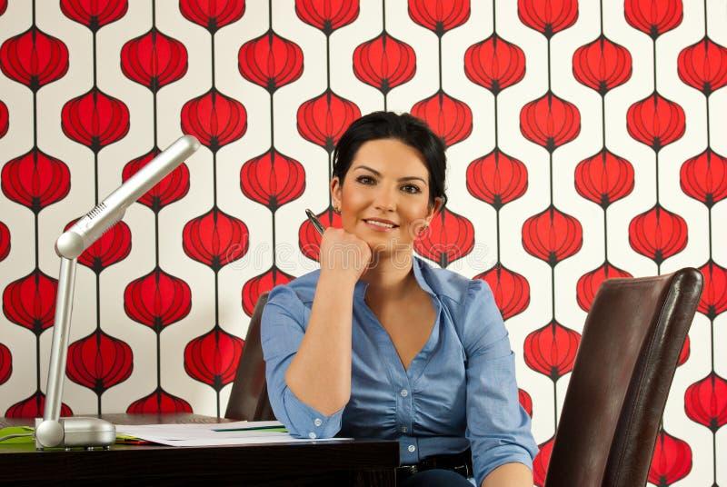 企业服务台坐的微笑的妇女 免版税库存图片