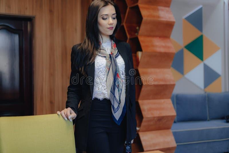 企业样式的年轻可爱的情感女孩在现代办公室或观众的一把椅子 免版税库存图片