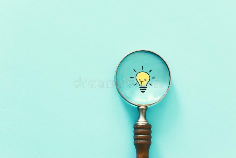 企业概念图象 放大镜和灯 除了别的以外发现最佳的想法和启发 免版税库存图片
