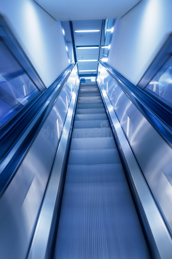 企业概念射击了导致在现代大厦的自动扶梯行动迷离 与生意相关的项目的完善的背景 免版税图库摄影