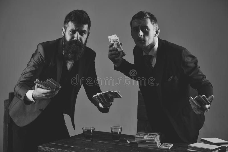 企业概念查出的成功白色 与现金的秘密交易 参与非法事务公司 人在与堆的桌上  库存图片