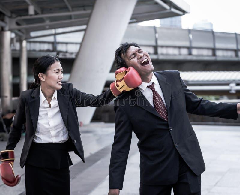 企业概念:衣服一致的佩带的拳击手套和猛击的商人` s面孔的年轻亚裔女商人 库存照片