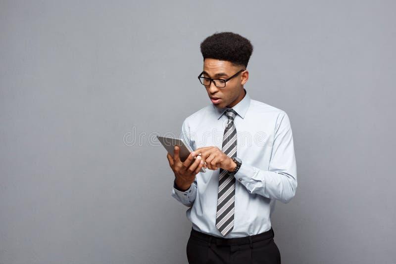 企业概念-冲击与某事的愉快的英俊的专业非裔美国人的商人在片剂 免版税库存照片