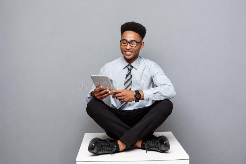 企业概念-发短信在数字式片剂的愉快的英俊的专业非裔美国人的商人对客户 图库摄影