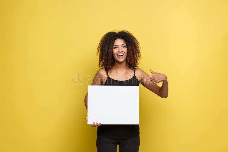 企业概念-接近的对简单的白色空白的画象年轻美丽的有吸引力的非裔美国人的指向的手指 库存图片