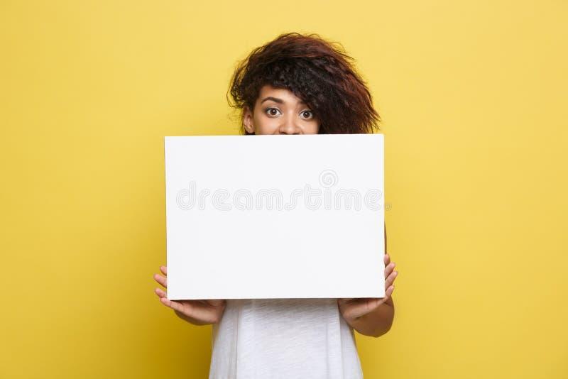 企业概念-接近的画象微笑年轻美丽的有吸引力的非裔美国人显示简单的白色空白的标志 免版税图库摄影