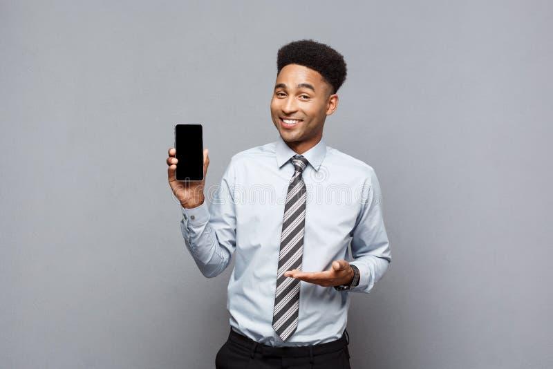 企业概念-显示手机的愉快的英俊的专业非裔美国人的商人对客户 库存照片