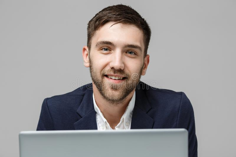 企业概念-演奏有微笑的确信的面孔的画象英俊的商人数字式笔记本 奶油被装载的饼干 免版税库存图片