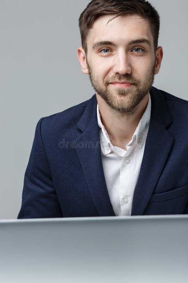 企业概念-看在膝上型计算机的衣服的画象英俊的严肃的商人工作 奶油被装载的饼干 库存照片