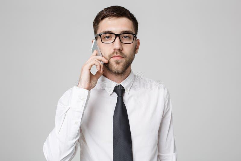 企业概念-衣服的画象年轻英俊的恼怒的商人谈话在看照相机的电话 空白 免版税图库摄影