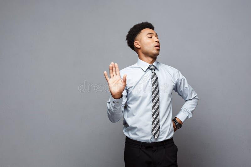 企业概念-被注重的非裔美国人的商人陈列停车牌画象用在灰色背景的手 免版税库存照片