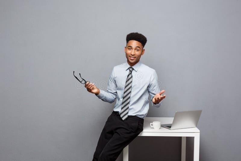 企业概念-非裔美国人的商人画象戴食用的眼镜的坐在书桌的咖啡使用膝上型计算机 库存图片