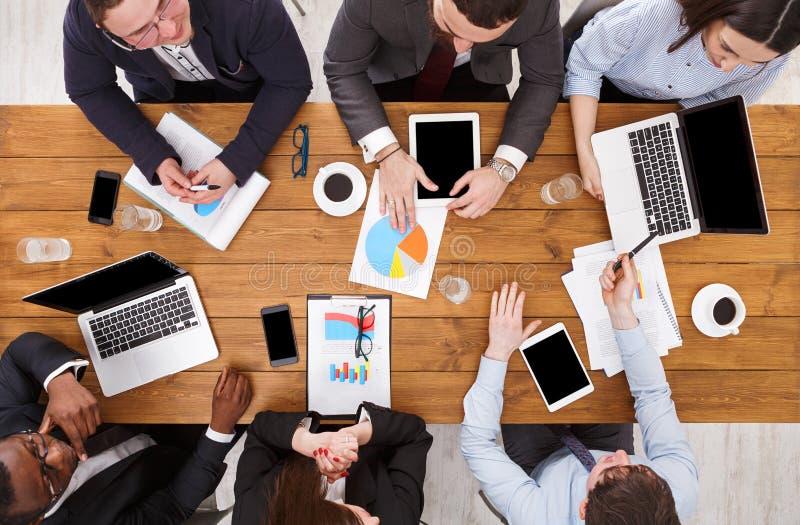 企业生意人cmputer服务台膝上型计算机会议微笑的联系与使用妇女 不同种族 工作者,发展战略,在办公室,木桌顶视图  免版税图库摄影