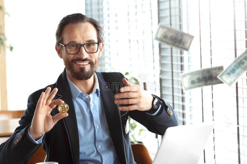 企业生活方式 坐在与选择cryptocurrency硬币的膝上型计算机投掷的去钞票的咖啡馆的玻璃的贸易商 免版税图库摄影