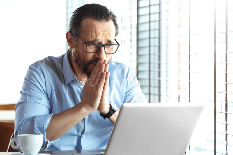 企业生活方式 坐在咖啡馆的玻璃的祈祷的贸易商看膝上型计算机为有利的投资 免版税库存图片