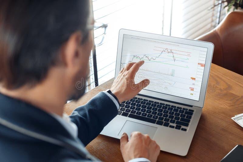 企业生活方式 贸易商在看贸易的图的咖啡馆坐膝上型计算机被集中的后面看法特写镜头 库存图片