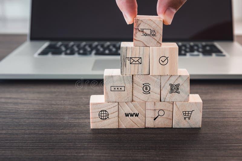 企业电子商务和购物媒介象概念,特写镜头眼线是拾起从堆的木立方体在计算机前面 图库摄影