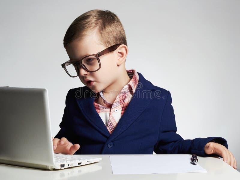 企业男孩 玻璃的滑稽的孩子写笔的 小的上司在办公室 免版税库存照片