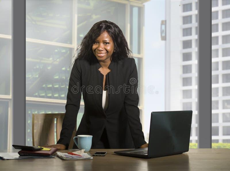 企业画象年轻愉快的可爱的黑人非裔美国人的女实业家微笑的确信常设成功在financi 免版税库存照片