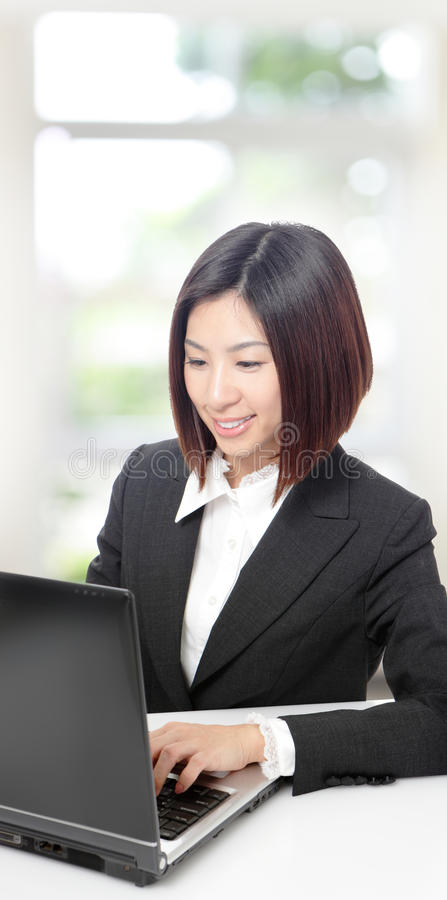 企业笔记本使用妇女的个人计算机微笑 库存图片