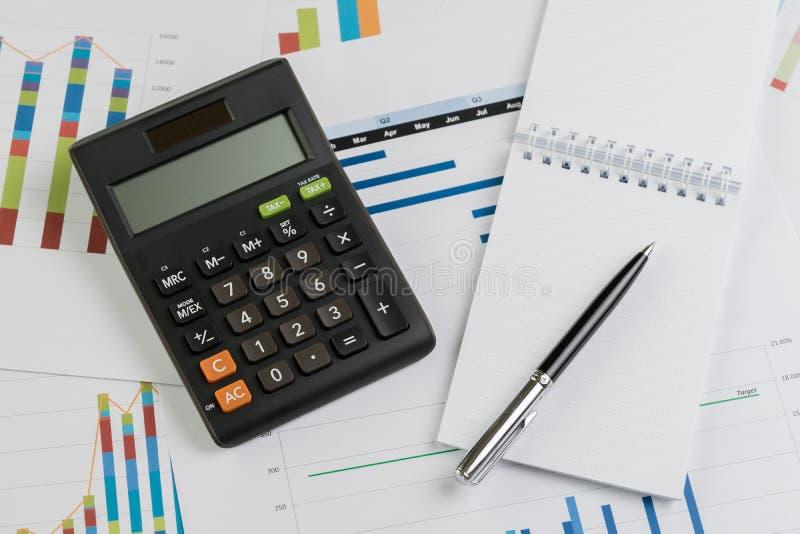 企业经营情况的财务或企业季度与纸笔记的工作考核概念、计算器、笔关于长条图和图 免版税库存图片