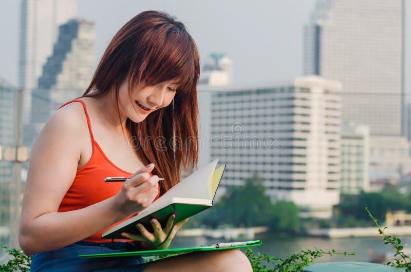 企业计算器概念货币 亚裔女商人是读和写书 库存图片