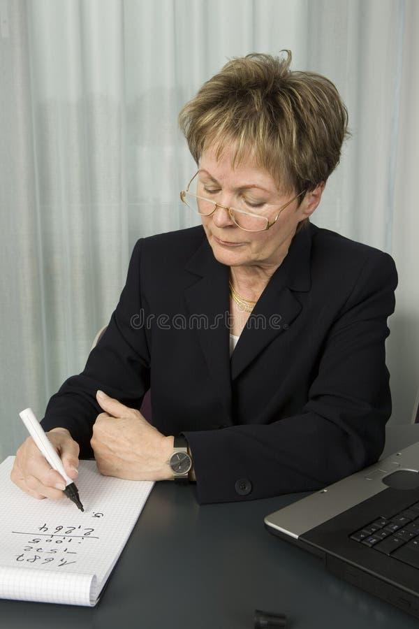 企业计算的高级妇女 库存照片