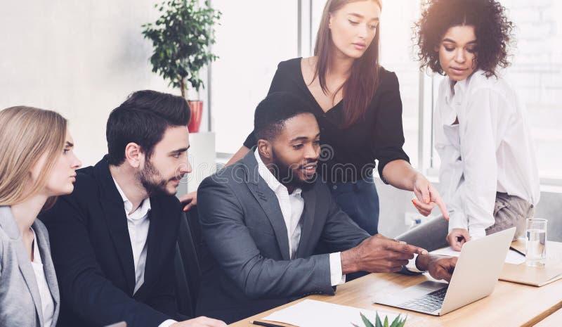 企业讨论 分析关于膝上型计算机的同事数据 免版税库存照片