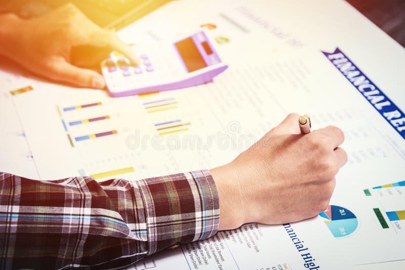 企业财务会计概念:使用计算器的商人手和财务覆盖在办公桌上的报告分析 免版税库存照片