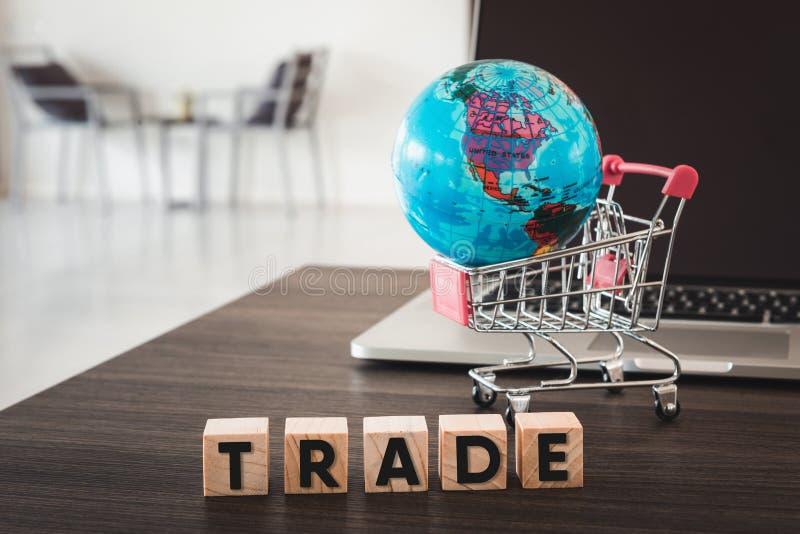 企业贸易和电子商务网上和财政概念 计算机、全球性模型、手推车和木立方体与文本 库存照片