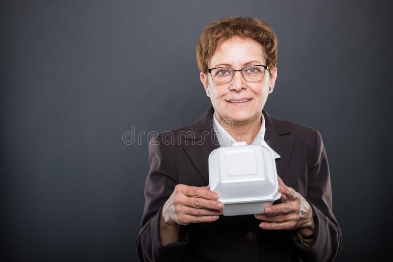 企业资深夫人画象拿着午餐盒的 免版税库存照片