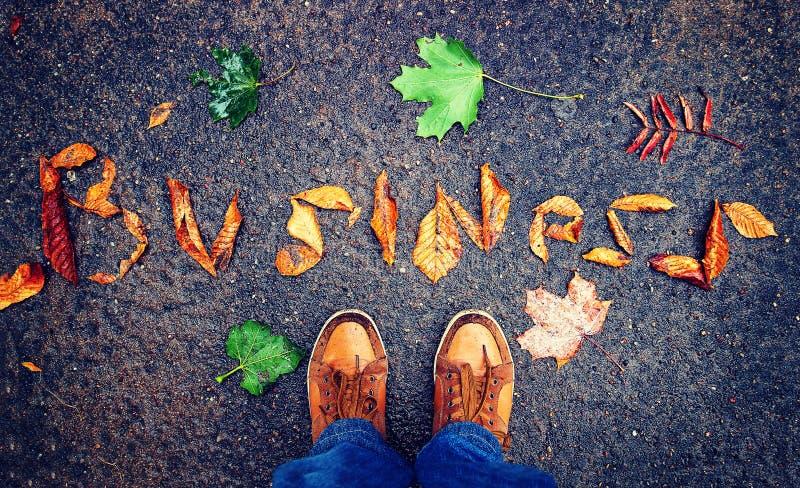 企业起动和起动概念 人的腿在词事务前面的从在沥青顶视图的叶子 图库摄影