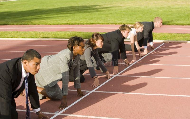 企业蹲下的线路开始跟踪的人们 库存图片