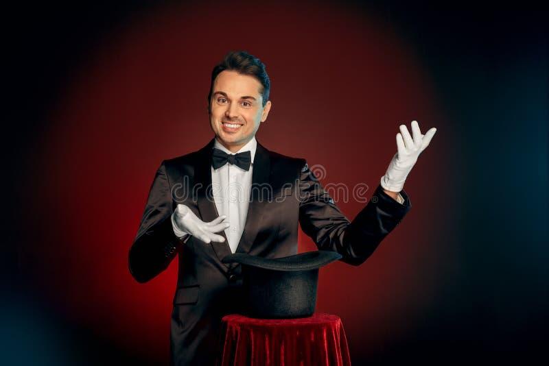 企业重活职业人专业工作 衣服的站立在墙壁上的魔术师和手套做与帽子的把戏在桌陈列 免版税库存照片