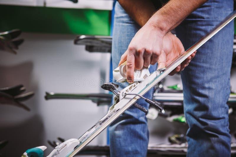企业销售滑雪设备题材和服务  年轻白种人人的手有山滑雪,检查并且调整f 图库摄影