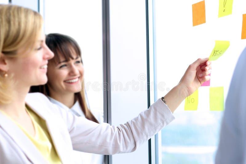 企业队与数字式片剂和贴纸一起使用在办公室 免版税库存图片